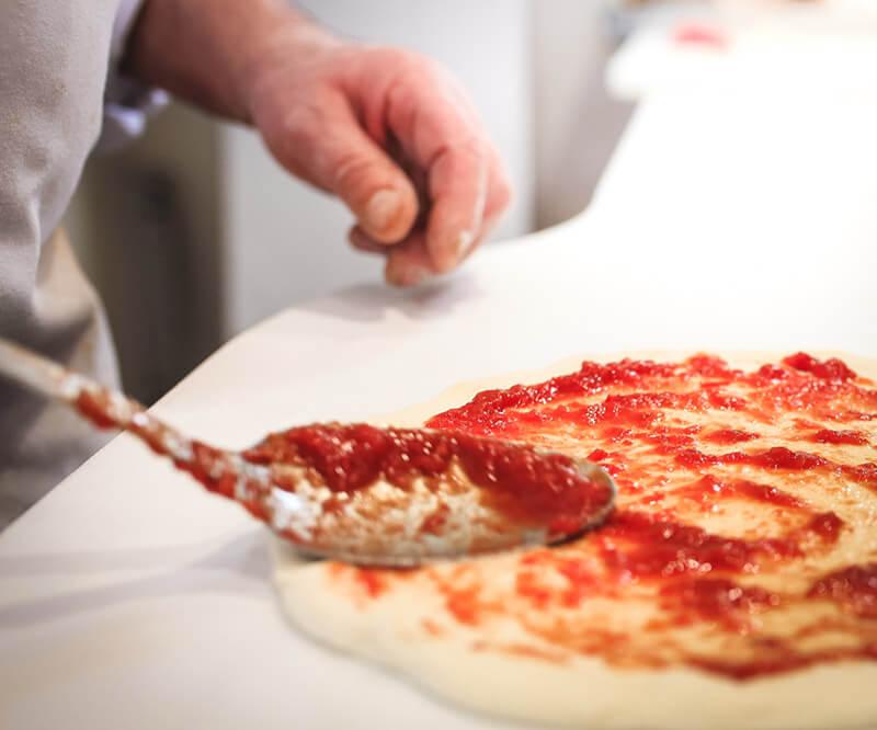 Un pizzaiolo étale de la sauce tomate sur une pate à pizza